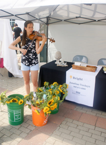 Laila entertaining the crowd with violin music at Jonathan Verduyn Real Estate's tent.