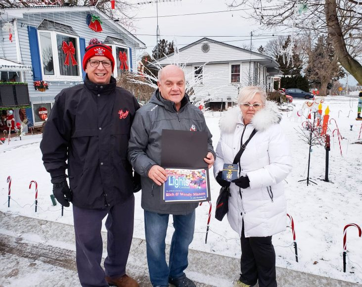 Councillor Dave Kadwell and Christine Hervé of Rona Grimsby present Rich Mason with his certificate and gift card at his home at 425 Elizabeth St. in Grimsby